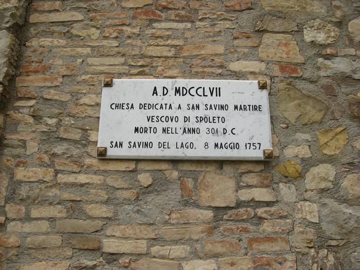 таблица на стене церкви в Сан Савино в Умбрии
